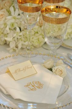 Lovely white and gold wedding Tablescape with monogrammed napkins. Love the bubble edge of the chargers.