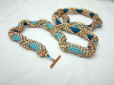Ocean Storm.  Beautiful summer ready bead crochet necklace!  This lovely beaded rope necklace is made with thousands of top quality glass seed beads.  The elegant teal and azure blue diamonds are perfectly set off by the gold dimensional edge beads!  The great colors and subtle waves are reminiscent of a warm storm on Caribbean seas – or a relaxing day at the beach!  www.LanmomOriginals.com