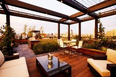 Exterior - Luxurious Contemporary Patio Area With Wood Floor Iron Pergola Brown Sofas Brown Table Brown Stools And City View: Modern Pergola...