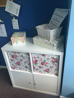 IKEA Kallax unit with two door inserts and floral storage boxes.
