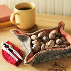 This rustic felt nut bowl is perfect for giving at a cozy holiday party. Cut two 10-inch squares -- one from felt and the other from woven cotton. Fold the edges of the cotton square and pin it to the felt. Stitch the squares together. Form the bowl by folding up the sides, sewing around the bottom, and leaving about 1-1/2 inches not sewn at each corner. Using embroidery floss, gather each corner with an X stitch.