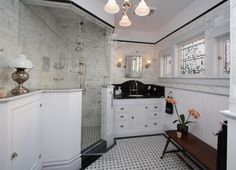 This Victorian bathroom design features a large custom shower, painted cabinets, bead board, leaded glass, wainscoting & subway tile.
