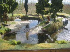 Base MDF et bord + mousse polystyrène. Canaux découpés poncés et spackle lissé (bancs sable/zones gué) Plate-forme sculptée et altérée au crayon. Roche = écorce de pin collée à chaud. Plusieurs couches mélangées a du café puis acrylique (tons terre de la rivière). Flocage = différentes couches et couleurs. 3 longueurs d'herbe = profondeur. Lit rivière =tons de terre variés + clairs pour zones peu profondes. Eau réaliste Woodland Paysages = 1 couche épaisse par endroits et 2 ailleurs. Arbres…