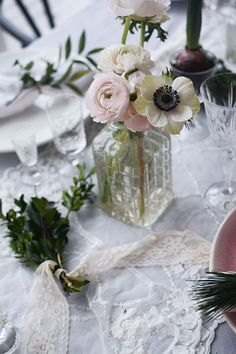 Pretty delicate anemone in vintage bottle, add lace and you've got a pretty table.