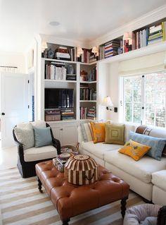 Corner bookshelf bordering ceiling around the room.