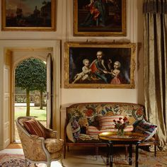 Robert Kime ~ An 18th century gilt-framed portrait hangs above a sofa in the hall beside a door leading to the garden