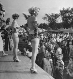 "Scantily clad women posing on platform in front of tent to stir up business for ""peep show"" on the crowded midway of the Michigan State Fair. Photograph by Francis Miller. Detroit, Michigan, September 1950."