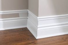 To make your baseboard more dramatic, add small pieces of trim to the top of existing baseboard, add a few inches and add another piece of moulding. Paint the wall and trim white. @ DIY Home