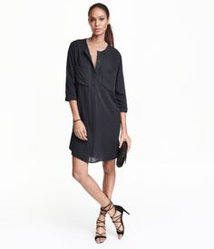 Straight-cut dress in woven viscose fabric. Round neckline, concealed button placket, chest pockets, 3/4-length sleeves, and slits at sides. Unlined.