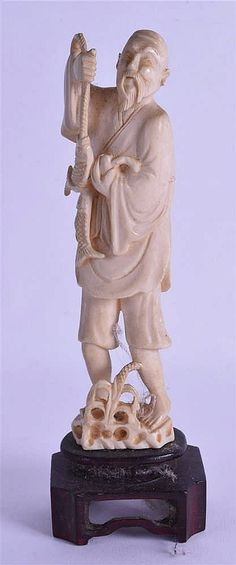 A 19TH CENTURY CHINESE CARVED IVORY FIGURE OF A FISHERMAN modelled holding