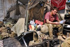 A soldier from 3rd Battalion, The Parachute Regiment, sits in his bed space at a checkpoint in Afghanistan reading letters from loved ones back home.