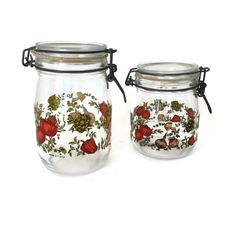 Two glass storage jars made in France.  These glass canisters have a hinged lid and have a rubber gasket to make then air tight.  The motif is vegetables and they have the words Niveau de Remplissage (fill line) and Made in France on them.  They were be wonderful as part of a French country kitchen