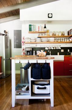 Floating wooden shelves at different lengths provides interest in the kitchen. the black back splash with red cabinets, wooden countertops, and a white farm sink make this kitchen feel homey and modern.