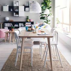 Zona pranzo con tavolo in impiallacciatura di frassino, sedie e sedia alta in bianco.