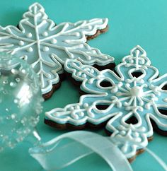 Icy blue frosting with white piping on dark brown cookies.
