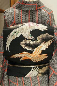 黒の地に、天高く勇壮に舞う二羽の鷹が織り出された名古屋帯です。
