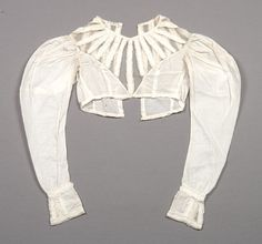 Bodice 1820–1830 Cotton, Silk Mesh. Bodice of fine white cotton: silk mesh yoke ending in deep V at center front and back; panels of cotton with self fabric piping and ruffles radiate from neckline to edge of yoke; self fabric covered buttons along center back close with loops; long leg-of-mutton style sleeves; slightly flared cuff trimmed with panels of cotton with self fabric piping and ruffles at wrist and cuff hem. Fine arts museums of San Francisco.