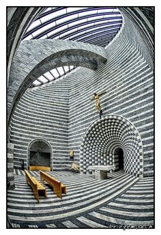 von dem Tessiner Architekten Mario Botta entworfene elliptische Kirche San Giovanni Battista aus Cristallina-Marmor des oberen Valle di Peccia sowie Gneis aus dem Valle Maggia mit einem Dach aus Eisen und Glas-