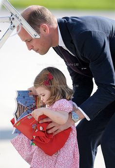 July 21, 2017: Princess Charlotte clutches her in-flight entertainment, a farewell gift from her visit to Germany, as she and Prince George board their flight home. A helping hand from Daddy Prince William for Princess Charlotte who wouldn't let go of her new books. #RoyalVisitGermany