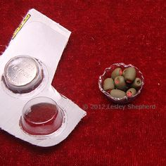 Rigid plastic packaging from a package of watch batteries is used to make a fluted 'glass' serving dish in dolls house scale.