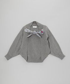 Little ladies will look all dolled up in this dainty shrug. A polka dot front tie makes the fit easy to adjust, while ribbed trim ensures a snug fit.