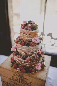Nahý dort ozdobený květinami a ovocem. (Naked wedding cake with flowers and fruits).