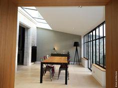 Une rénovation globale est opérée afin de mettre en valeur les cheminées en marbre, miroirs, escalier en bois... Une façade type verrière atelier se décline sur 6m de long et en toiture, une verrière de 4,50m de long rend cet espace très lumineux. La pierre au sol et au mur, le zinc de couleur noire en toiture, les menuiseries acier, le cuivre et les carreaux de ciment, sont utilisés ici et là. Des enfilades années 60 sont chinés et reconvertis en meubles de salle de bain. Renovation Facade, Architecture, Conference Room, Kitchen, Table, Furniture, Home Decor, Woodwork, Wall