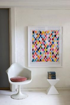 DIY artwork idea.  Maybe use paint strip squares, triangles, or circles.  Maybe use silver thumbtack at top of each shape?