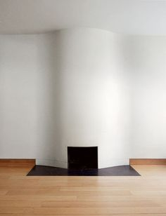 The Calatrava Family's Upper East Side Compound. The Fireplace. The white wall bulges woozily, and the negative space appears to throw a shiny black shadow on the floor.