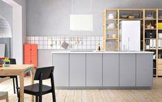 En stor, moderne og grå køkkenø med VEDDINGE fronter, IVAR reoler af massiv fyr og IKEA PS 2014 spisestuesæt