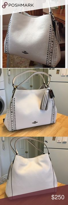 White Coach Bandana Rivets Shoulder Bag Coach Bandana Rivets Edie 31, white shoulder bag, gunmetal chalk with charm. This gorgeous bag was used one time. There is an unnoticeable scuff just below the side lock (see 6 th pic). Bought at Macy's, it's too small for me. Perfect condition inside and out except scuff noted above (you probably won't be able to see it in pic). Non smoking home. No trades. Coach Bags Shoulder Bags