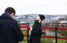 Kvinne ser opp på himmelen og noterer i en rød notatbok