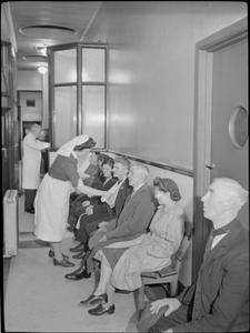 FACTORY WELFARE WORK: WELFARE AT PILKINGTON'S GLASS FACTORY, ST HELENS, LANCASHIRE, ENGLAND, UK, 1944 D 20084  A nurse checks on a war worker wearing a sling, sitting amongst a group of injured men and women as they wait to see a medical officer in the Waiting Room of the Sheet Works Surgery at the Pilkington glass factory in St Helens. According to the original...