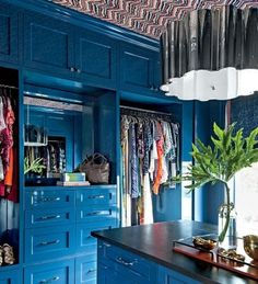 A 175-square-foot closet is made over into a glamorous, glossy cobalt dressing den with a window for natural light, plenty of built-in storage and an island that provides space for folding clothes and storing accessories. | Via SouthernLiving.com