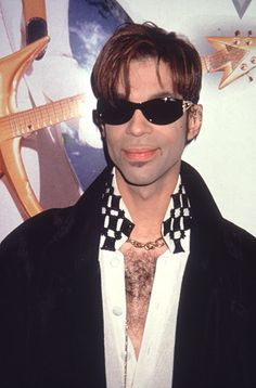 """1998 Shades, a big coat and a checkered white shirt comprise the look Prince wears in 1998 in New York City, the year he released his """"Crystal Ball"""" box set. 