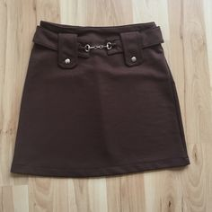 Brown XS Skirt Stretchy material with elastic waist. I think I got this from kids department because size listed as 10...I'm XS-S and it fits. Cute belt detail in front. Laying flat: waist 12in (14stretched) hip 15in  length 15in Skirts Mini