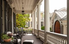 Spacious wrap around porch with upholstered outdoor furniture and rocking chairs  SLC INTERIORS - Interior Design - Charleston, SC
