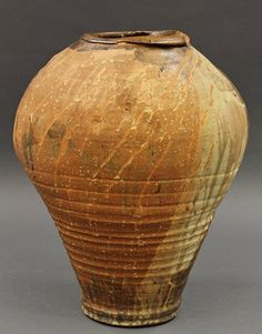 Monumental studio art pottery vase, late 20th century. Hand thrown stoneware of abstracted ovoid form with streaked glazes in browns, tans and creams, 18h x 12w.