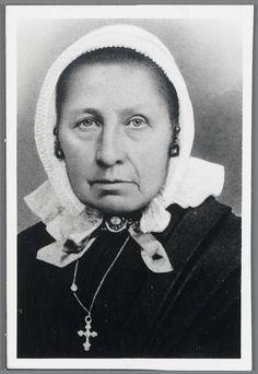 Elizabeth Koekkoek-Mentink in Veluwse streekdracht, 1860-1890 Elizabeth is in 1801 geboren in Vaassen. Ze draagt een cornetmuts, met fijn geplooide voorstrook en grof geplooide achterstrook. Op ooghoogte zijn twee mutsenbellen in de voorstrook gehangen. Om haar hals draagt Elizabeth een strik. Op de knoop is een rond voorwerp te zien. dit is een broche of de sluiting van een halssnoer. Op haar borst draagt ze een kruisje aan een ketting. #Gelderland #Veluwe #nieuwedracht #Epe