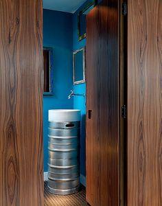A designer de interiores Luciana Penna trocou a coluna da cuba no lavabo por um barril