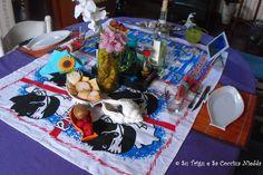 Tavola sarda imbandita con i 4 mori, conchiglie, delizie sarde, pane sardo alla ricotta fatto in casa da Tiziano, piatto a forma di pesce in attesa di essere riempiti di bontà. Tutto questo nella sala da pranzo di Su Trigu e Sa Cocciua Niedda