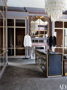 In the husband's dressing room, a '50s Barovier & Toso chandelier complements a '30s overmantel mirror; the custom-made packing table features nickel pulls and backplates by H. Theophile, and the silk carpet is by Beauvais.