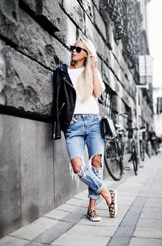 fall street style - ripped and cuffed boyfriend jeans + a white top and black leather jacket. Worn with leopard slip on sneakers.