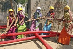 Indian laborers work to lay a cable for an electricity company in Ahmadabad, India, on March 8, 2013. (AP Photo/Ajit Solanki)