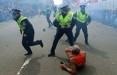 IlPost - Boston, Stati Uniti - Un atleta a terra – Bill Iffrig, di 78 anni – e tre poliziotti vicino alla linea del traguardo, subito dopo la seconda esplosione dell'attentato alla maratona di Boston, il 15 aprile 2013. (AP Photo/The Boston Globe, John Tlumacki)