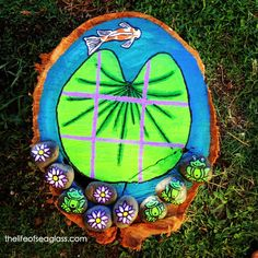 A lily-pad tic-tac-toe game I made for the garden for my daughter to play with.  I painted the rocks with frogs, flowers, and log surface with acrylic and then sprayed it all with clear coat.