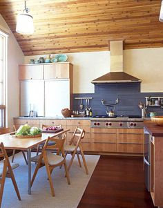 Hans Wegner table and chairs in oak complement the kitchen's alder wood cabinetry, with the subtlest contrast.   - HouseBeautiful.com