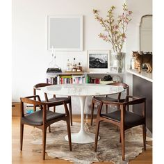 dining room. tulip table black dining chairs hide rug