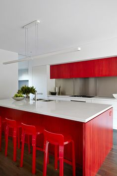 A family home featuring vibrant red accents by Melbourne-based interior design firm Nexus Designs. Artemide talo suspension light