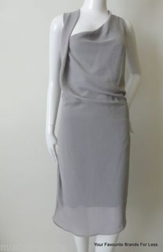 Satch-Dress-Size-6-10-or-US-2-6-Silver-Made-in-Australia This draped shoulder style dress is in a silver, slightly crinkled material and has an exposed zip on the upper back.  It has a black attached tie belt which can be tied at the front, back or side.  It has an asymmetric hem and is fully lined.  Size 6 (US 2) This could fit bigger sizes depending on whether the wearer would like it loose or fitting.